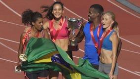 Atletas felices que saltan con la victoria brasileña del júbilo de la bandera, competencia de deportes almacen de metraje de vídeo