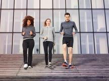 Atletas jovenes que van abajo al aire libre en las escaleras de la ciudad Imagen de archivo