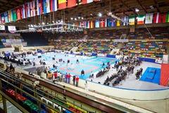 Atletas, jueces, espectadores en la pequeña arena deportiva Foto de archivo