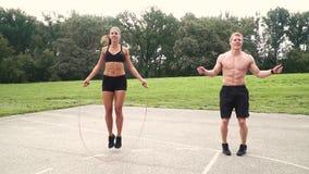 2 atletas musculares saltan con el cordón de la primavera almacen de video
