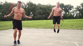 2 atletas musculares saltan con el cordón de la primavera almacen de metraje de vídeo