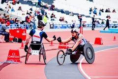 Atletas nas cadeiras de rodas que agitam as mãos Fotografia de Stock Royalty Free