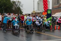 Atletas parapléjicos de la silla de ruedas que compiten con en maratón de la calle fotos de archivo