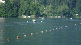 Atletas profesionales que propulsan los barcos en el agua, entrenamiento, deporte del rowing metrajes