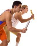 Atletas que compiten con el relais Fotos de archivo libres de regalías