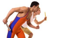 Atletas que compiten con el relais Fotografía de archivo libre de regalías