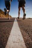 Atletas que corren en la carretera nacional Fotografía de archivo libre de regalías