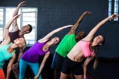 Atletas que doblan mientras que ejercita en gimnasio Imágenes de archivo libres de regalías