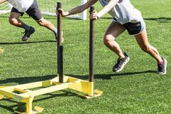 Atletas que empujan los trineos cargados en un campo del césped Fotografía de archivo libre de regalías