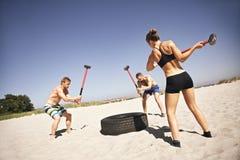 Atletas que hacen entrenamiento del crossfit en la playa Imágenes de archivo libres de regalías