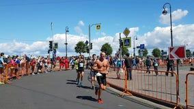Atleten bij één van de draaien van de marathon van St. Petersburg Steun van toeschouwers bij een afstand stock footage