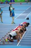 Atleten bij beginlijn van 100m sprintlooppas Stock Foto's