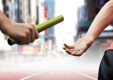 Atleten die de knuppel overgaan tijdens relaisras tegen stadsgebouwen stock afbeeldingen