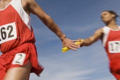 Atleten die Knuppel in Relaisras overgaan stock fotografie