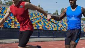 Atleten die relaisras op leeg stadion opleiden, groepswerk, aspiratie om te winnen stock video