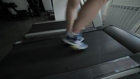 Atleten` s voeten op de tredmolen stock videobeelden
