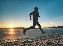 Atletenagent die op strand bij bevroren meer binnen zonsondergang lopen royalty-vrije stock foto