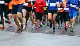 Atletenlooppas tijdens de regenachtige Marathon Stock Fotografie