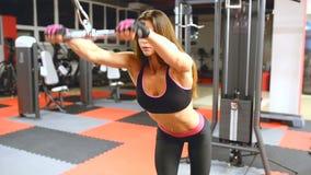 Atletenmeisje in sportkleding die en haar wapens en schouders in gymnastiek uitwerken opleiden stock videobeelden