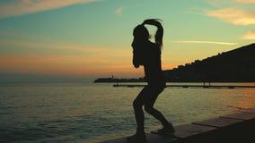 Atletenoverzicht het in dozen doen in lucht op overzees kuststrand op zonsondergang stock video