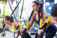 Atletenvrouw die duw UPS met trxfitness riemen in de sport van de de training gezonde levensstijl van het gymnastiekconcept doen stock foto