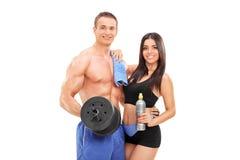 Atleti attraenti che posano con l'attrezzatura di forma fisica Fotografia Stock
