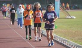 Atleti di atletica per seguire il percorso degli anziani in buona salute a Immagine Stock