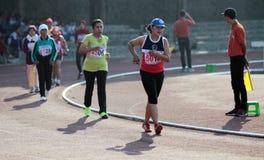Atleti di atletica per seguire il percorso degli anziani in buona salute a Immagini Stock