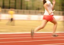 Atleti femminili che corrono sulla pista, il Mo sfocato Immagine Stock