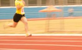 Atleti femminili che corrono sulla pista, il Mo sfocato Fotografie Stock Libere da Diritti