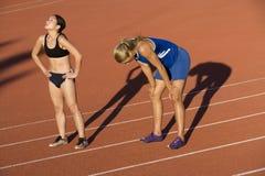 Atleti femminili stanchi sulla pista di corsa Fotografie Stock