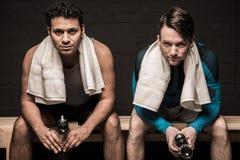 Atleti maschii che riposano allo spogliatoio della palestra Immagini Stock