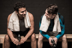 Atleti maschii che riposano e che conversano allo spogliatoio della palestra Fotografia Stock