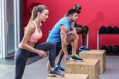 Atleti muscolari che fanno gli stretchings della gamba Fotografia Stock