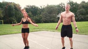 2 atleti muscolari saltano con il cavo della molla archivi video