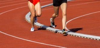 Atletiekmensen die op het spoorgebied lopen Zonnige dag royalty-vrije stock afbeeldingen
