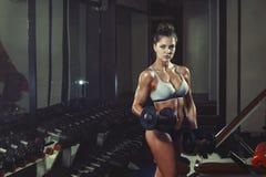 Atletisch jong meisje die een geschiktheidstraining met domoren in de gymnastiek doen Royalty-vrije Stock Fotografie