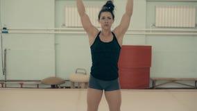Atletisch meisje die in gymnastiek opwarming van wapenspieren doen stock video