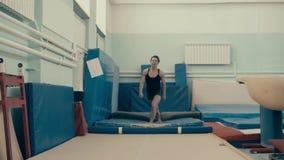 Atletisch meisje die in gymnastiek terug salto mortale doen stock footage