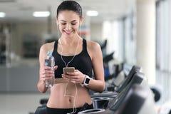 Atletisch meisje die smartphone in een gymnastiek gebruiken stock foto