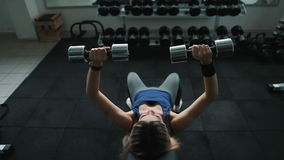 Atletisch meisje in gym do dumbbell pers op een hellingsbank stock footage