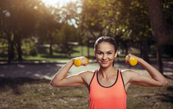 Atletisch meisje met domoren die haar spieren aantonen Royalty-vrije Stock Foto's