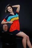 Atletisch meisje met een bal in kleurrijke kleding in studio op donkere bedelaars stock fotografie
