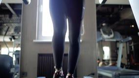 atletisch meisje in zwarte beenkappen en mooie benen bezet op een tredmolen stock footage