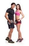 Atletisch paar - man en vrouw met domoren op het wit Royalty-vrije Stock Afbeeldingen