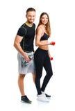 Atletisch paar - man en vrouw met domoren op het wit Royalty-vrije Stock Foto's