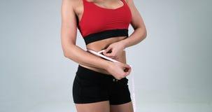 Atletisch vrouwelijk lichaam waar zij met band de buik aan witte achtergrond meet 4K stock footage