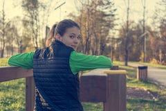 Atletisch wijfje die over haar schouders de post van de tricepsoefening bekijken royalty-vrije stock fotografie