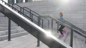 Atletische geschiktheidsvrouw die in stedelijke stad die met oortelefoons lopen aan muziek luisteren stock videobeelden