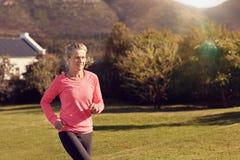 Atletische hogere vrouwenjogging in openlucht op zonovergoten ochtend in natu royalty-vrije stock afbeelding